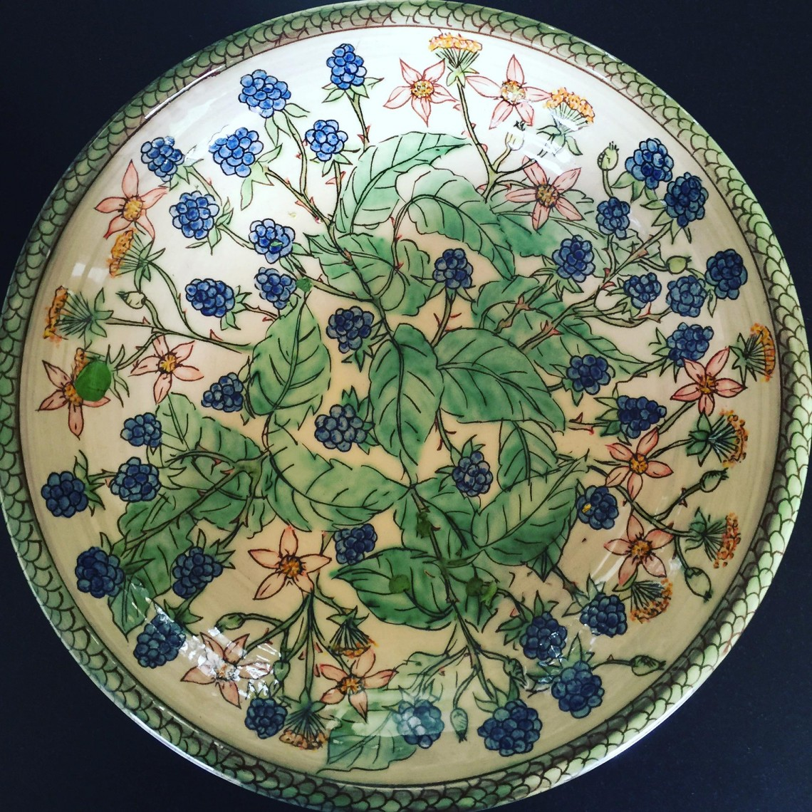 A hand painted pottery charger decorated wild bramble leaves, brambles and pink and yellow wildflowers. Handmade by Peter Thomas of Tower House Pottery, Berwick Upon Tweed, Northumberland