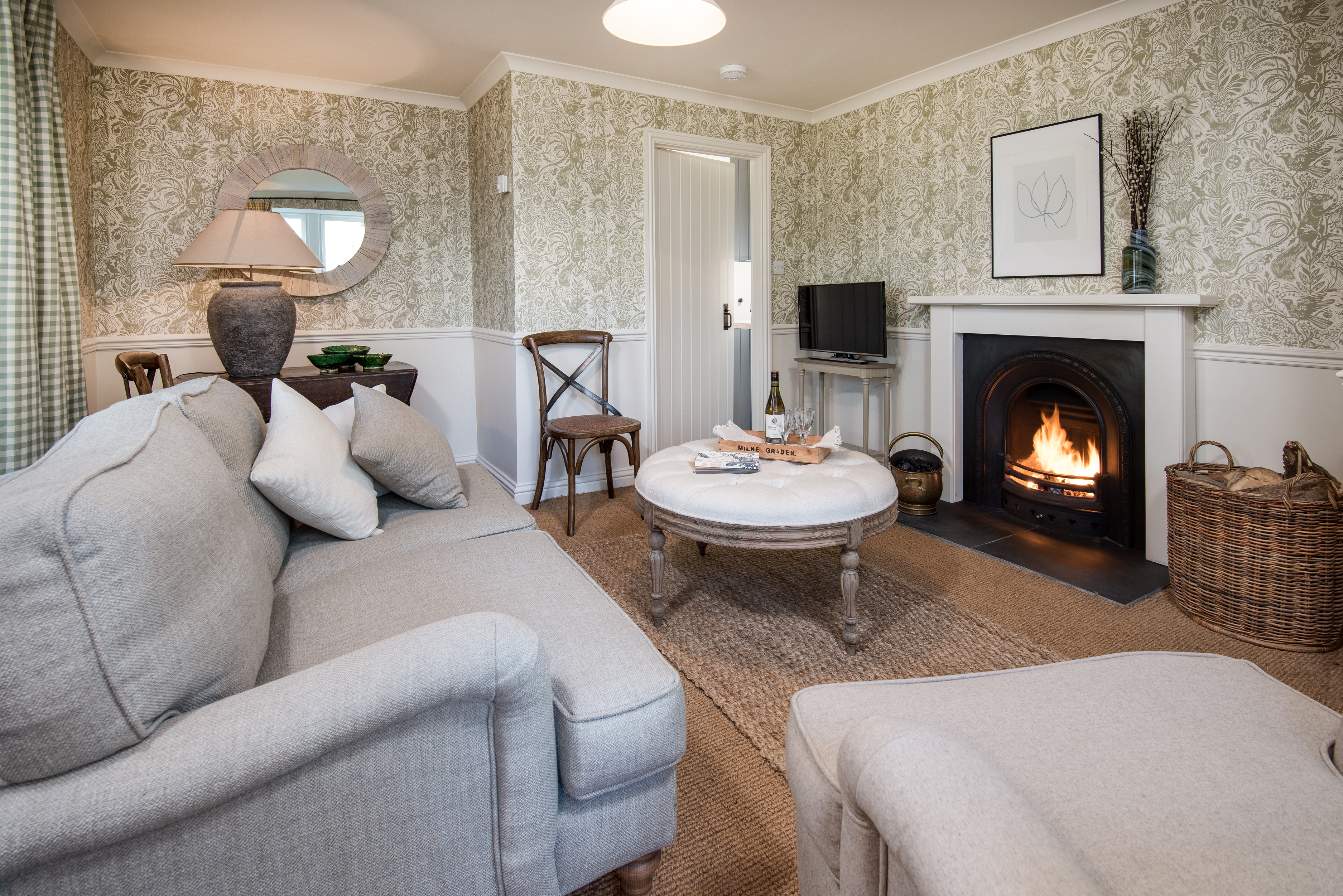 Milne Graden holiday cottage North Lodge Lounge featuring Harris Tweed Chelsea Textiles designer wallpaper open fire