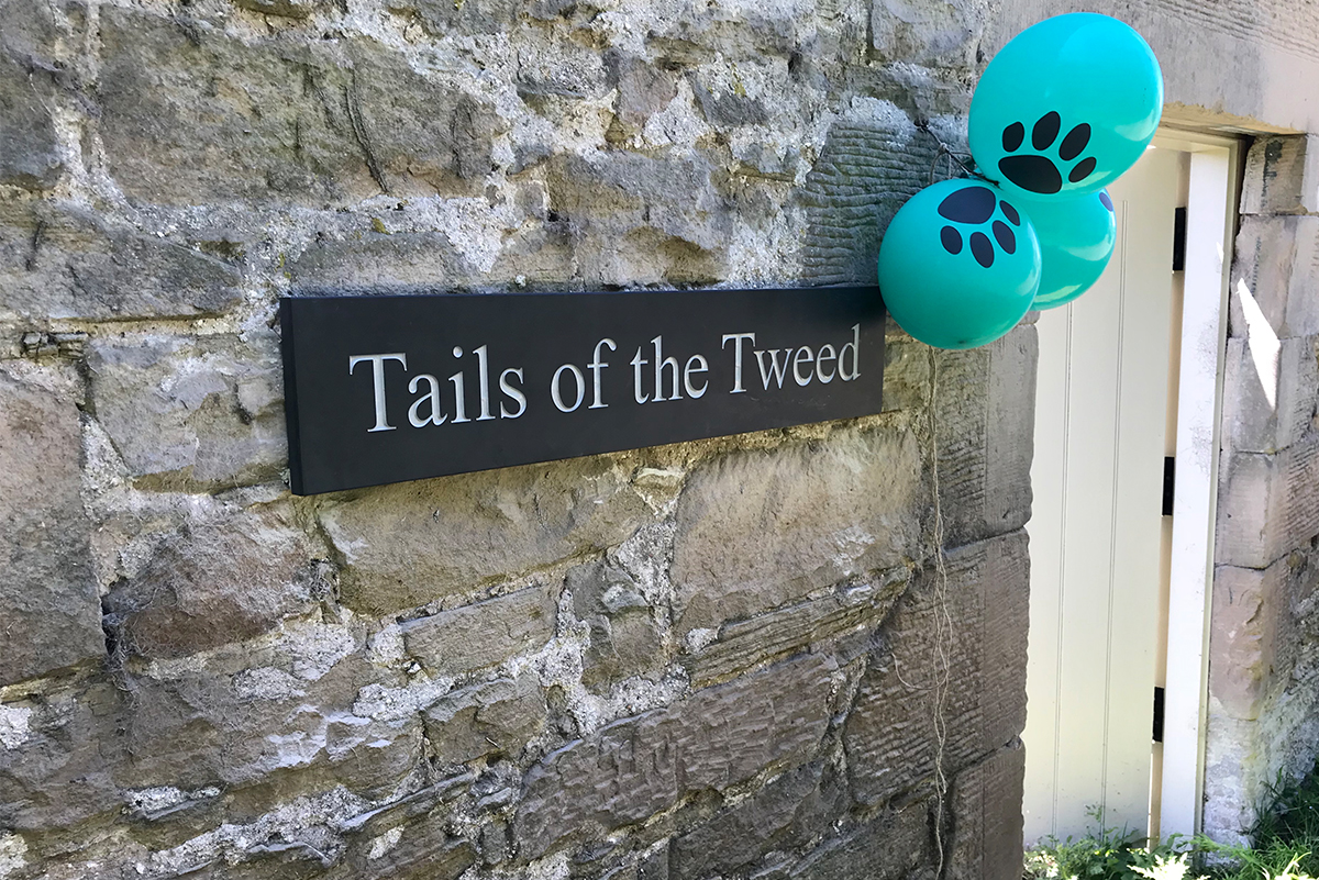 Tails_of_the_tweed_dog_park_sign_with_paw_print_ballons