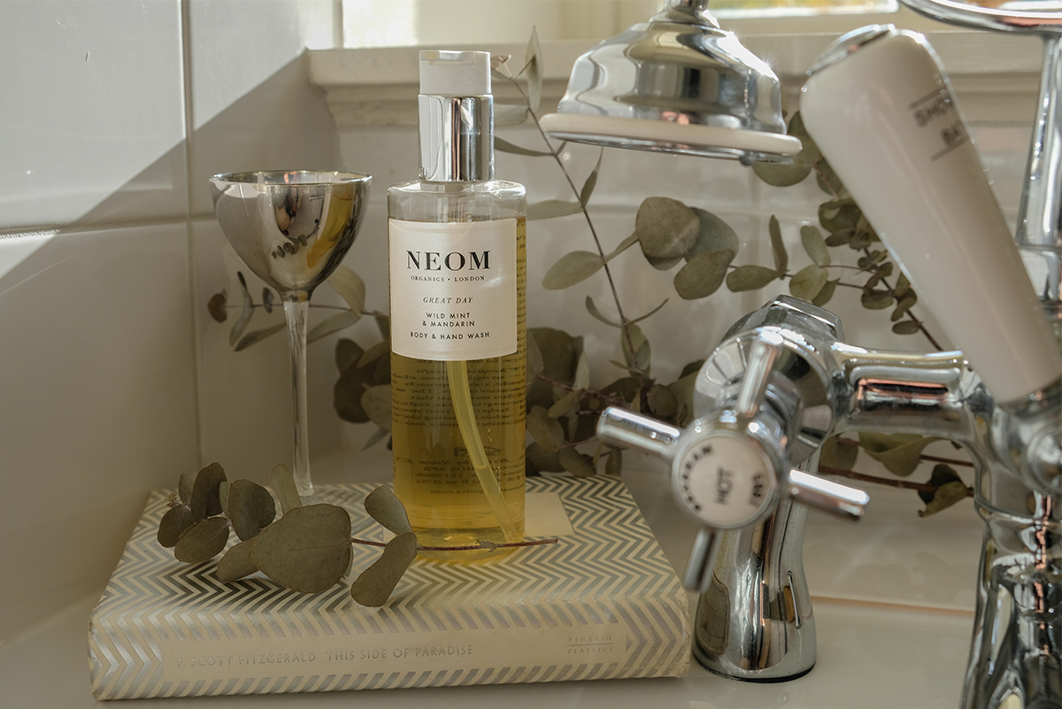 Milne-Graden-Neom-A-Scent-to-Make-You-Happy-Body_wash-on-bath-with-book-and-glass-in-Hamilton-House-Holiday-Cottage-