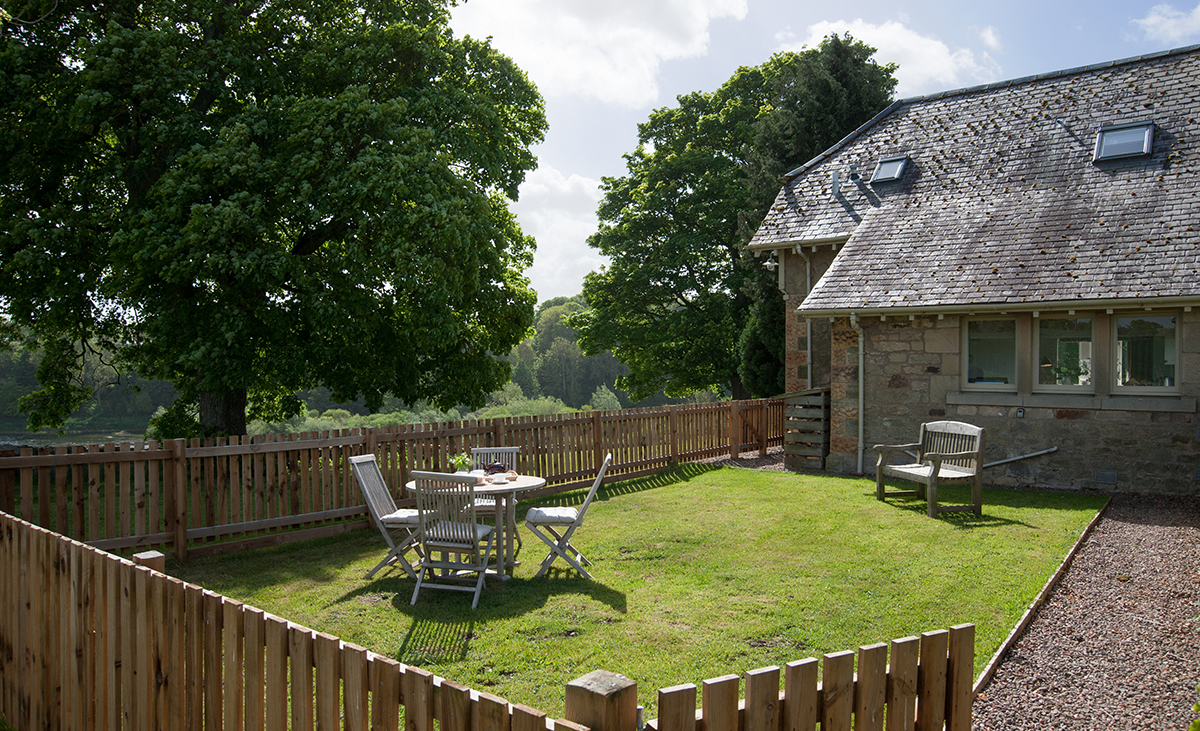Looking-over-wooden-fence-to-outdoor-table-and-chairs-at-Tweedside-Holiday-Cottage-Dog-Freindly-Enclosed-Garden