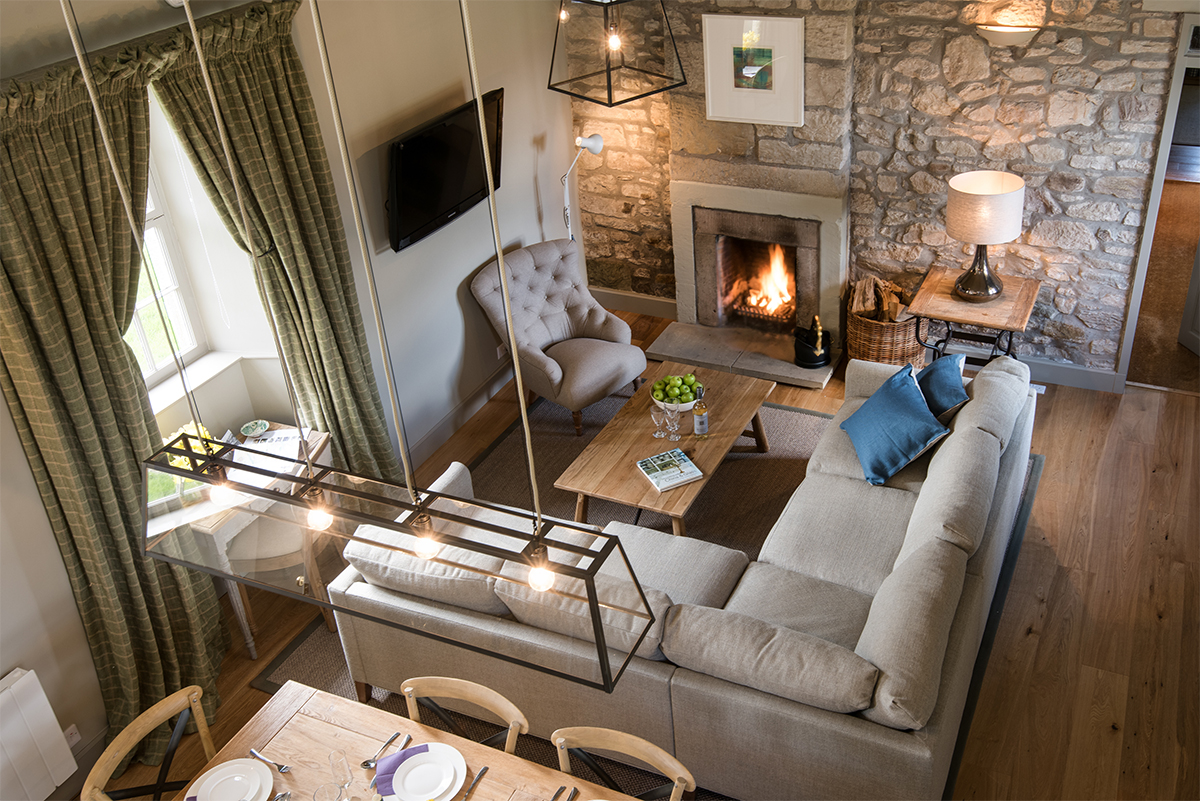 Milne-Graden-School-House-Holiday-Cottage-open-plan-Dining-Living-Area-with-original-btc-lantern-suspened-above-dining-table