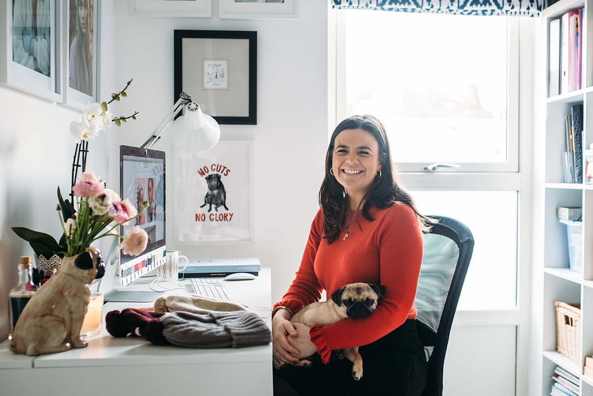 Milne-Graden-Press-Rosie-Sugden-Cashmere-Rosie-sitting-at-her-desk-with-pug-dog